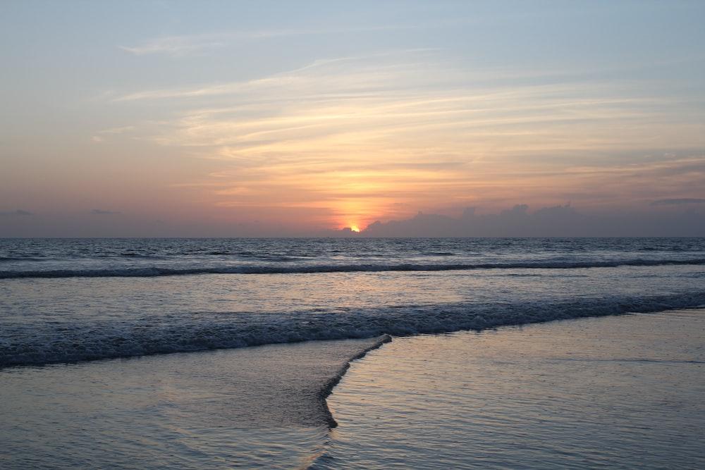sea waves crashing on shore during sunset