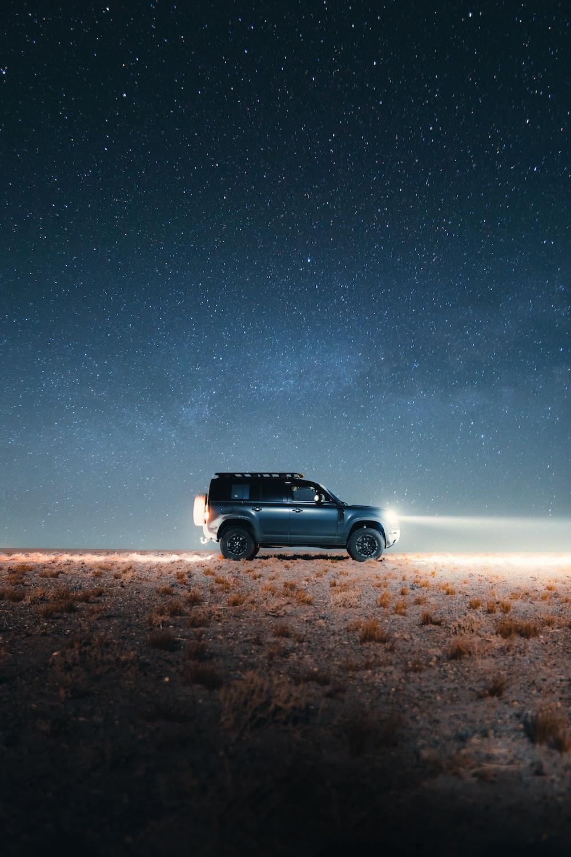 black suv on brown field under starry night