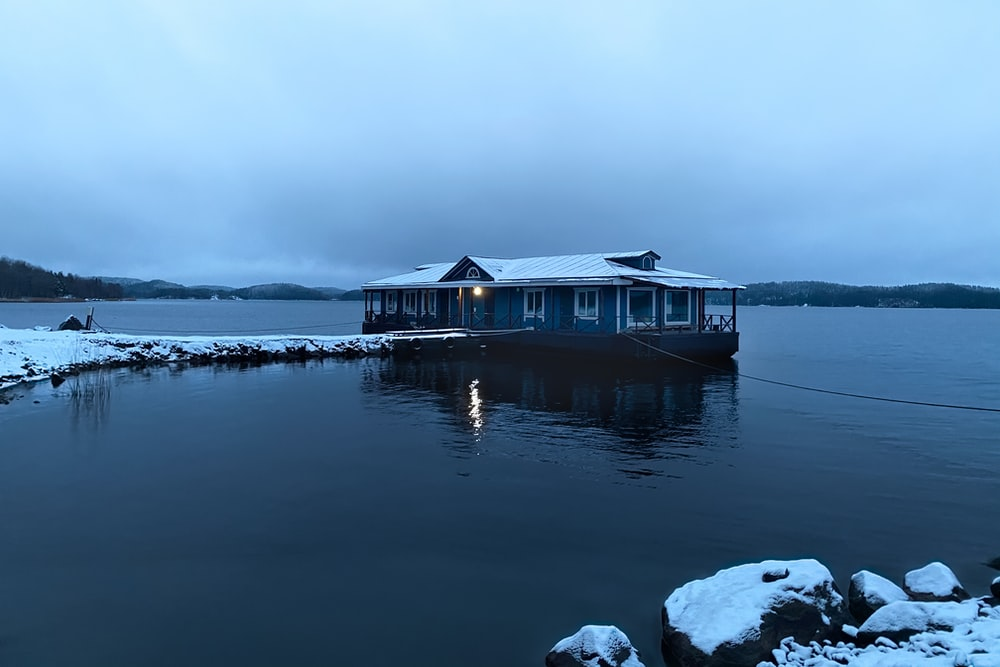 brown wooden house on snow covered ground near body of water during daytime