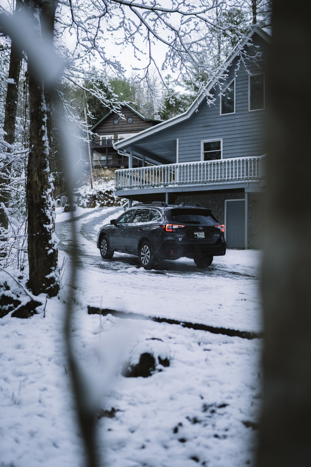 black suv parked near white wooden house during winter