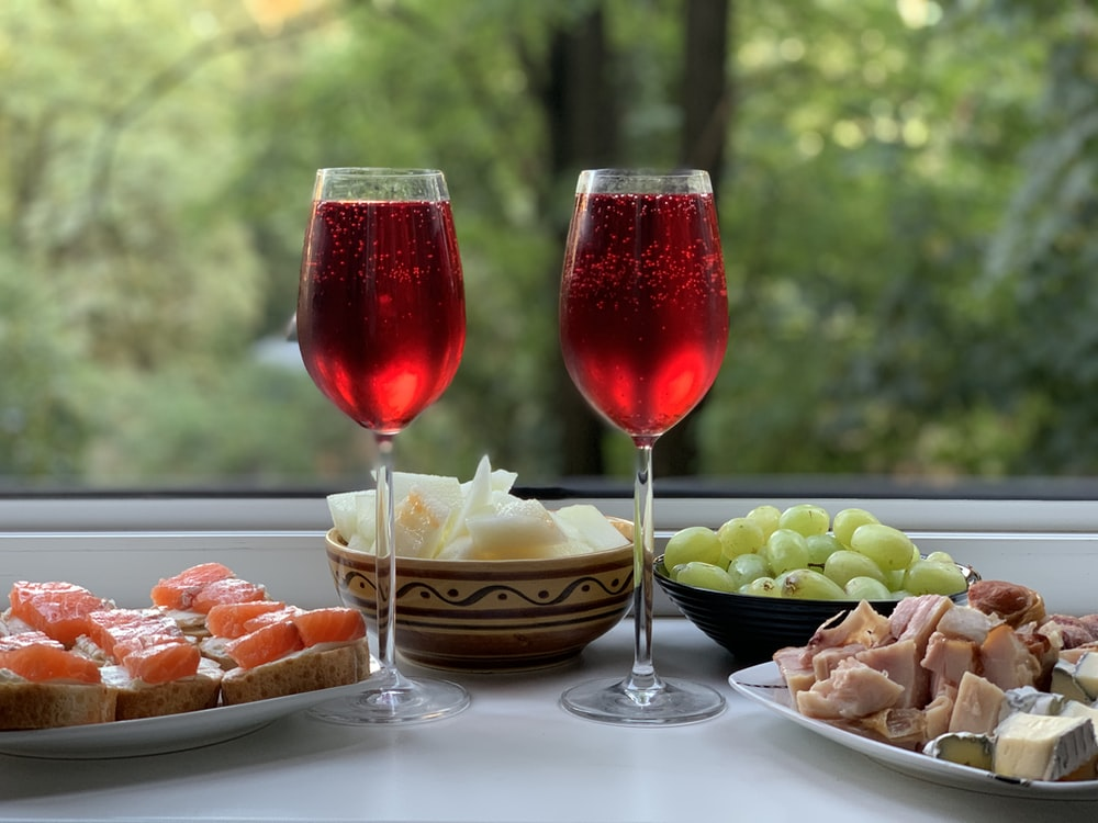 two wine glasses with red wine on table