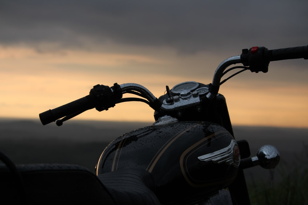 black motorcycle on the beach during sunset