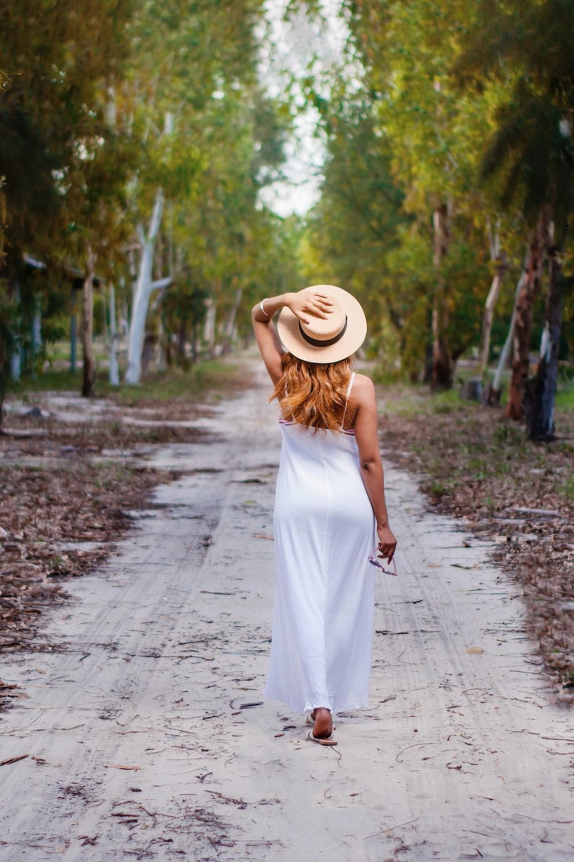 woman in white dress walking on pathway