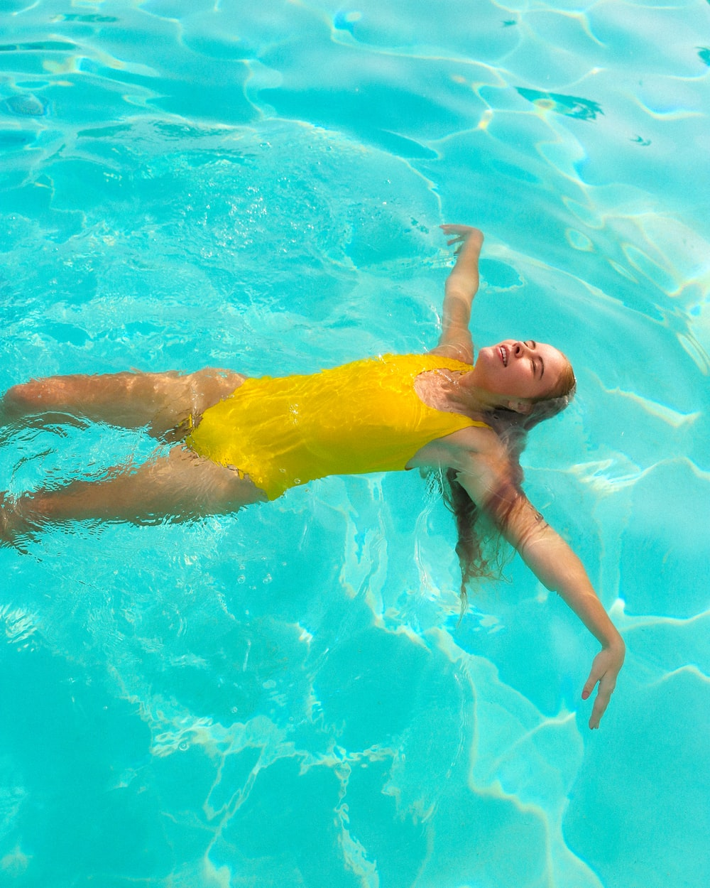 woman in yellow swimsuit in water