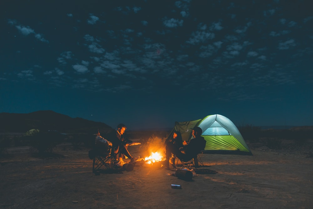 people sitting on camping chairs near bonfire during night time