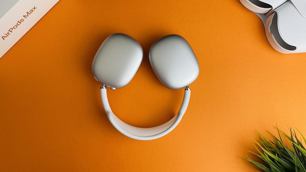 white and orange headphones on orange surface