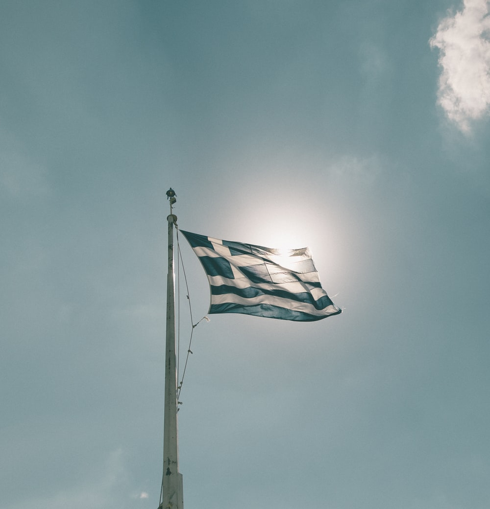 blue and white flag under cloudy sky