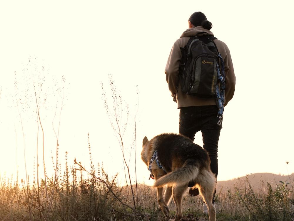 携带黑色和棕色的德国牧羊犬的黑夹克的男人