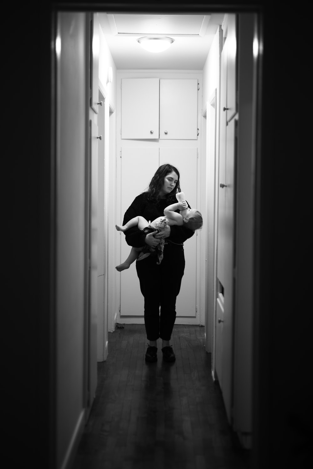 woman in black long sleeve shirt carrying baby in grayscale photography
