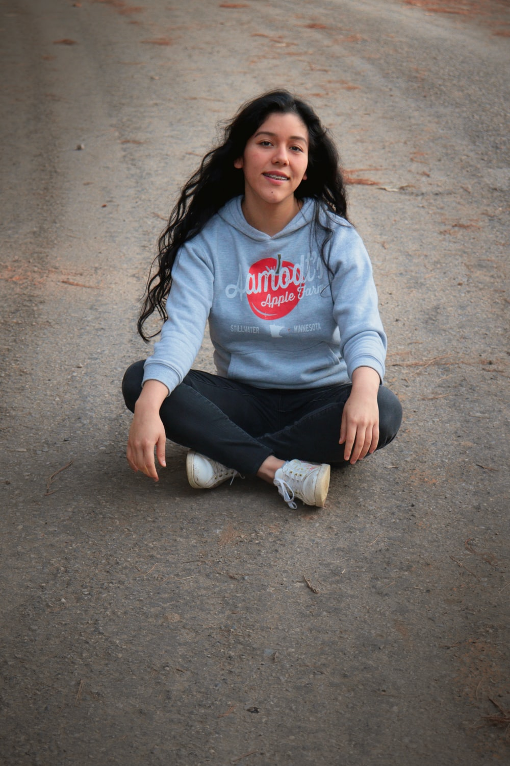 woman in white and red long sleeve shirt and black pants sitting on gray concrete floor