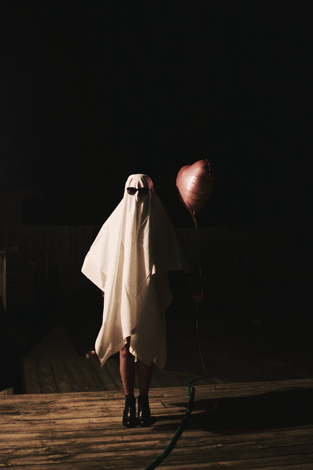 person in white robe standing on brown wooden floor