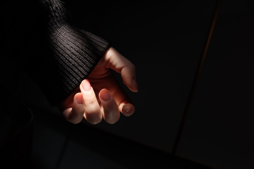 persons hand with orange manicure