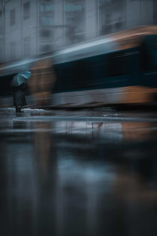 person in black jacket walking on wet road