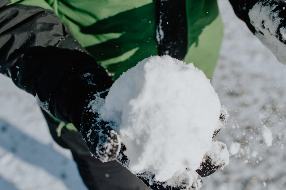 person in green and black jacket holding snow