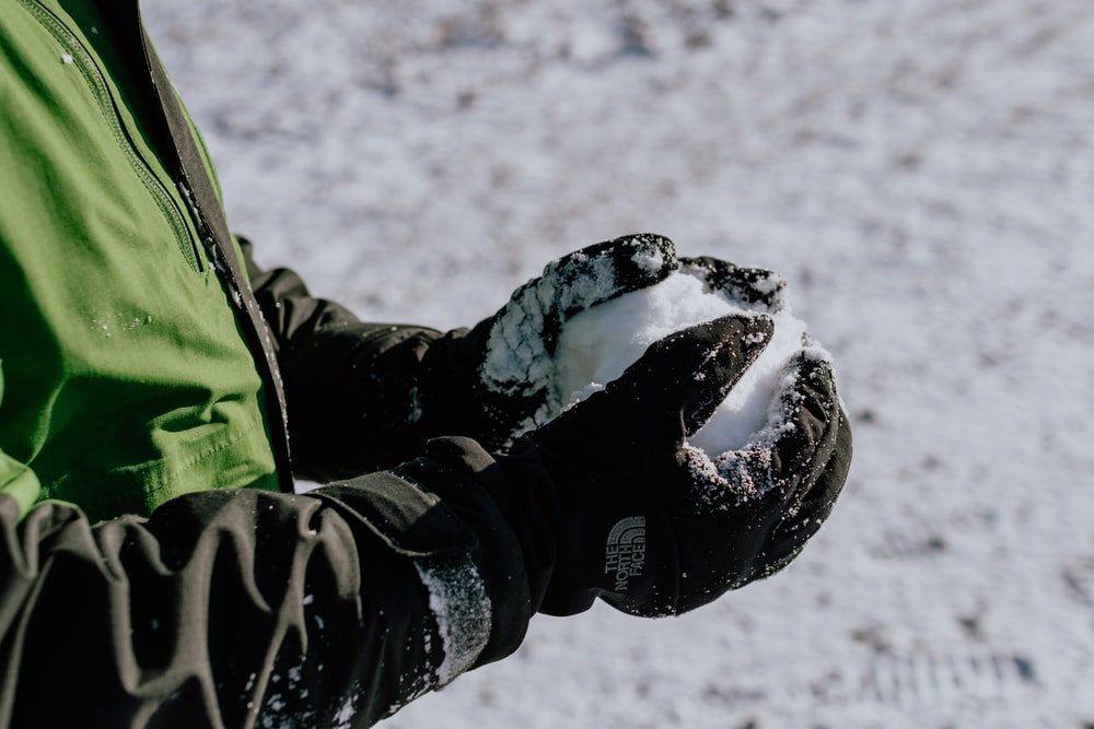 person in green and black jacket and black pants walking on snow covered ground during daytime
