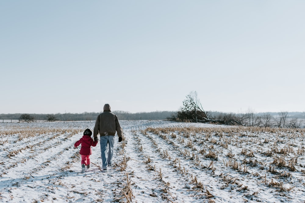 man and woman walking on snow covered field during daytime