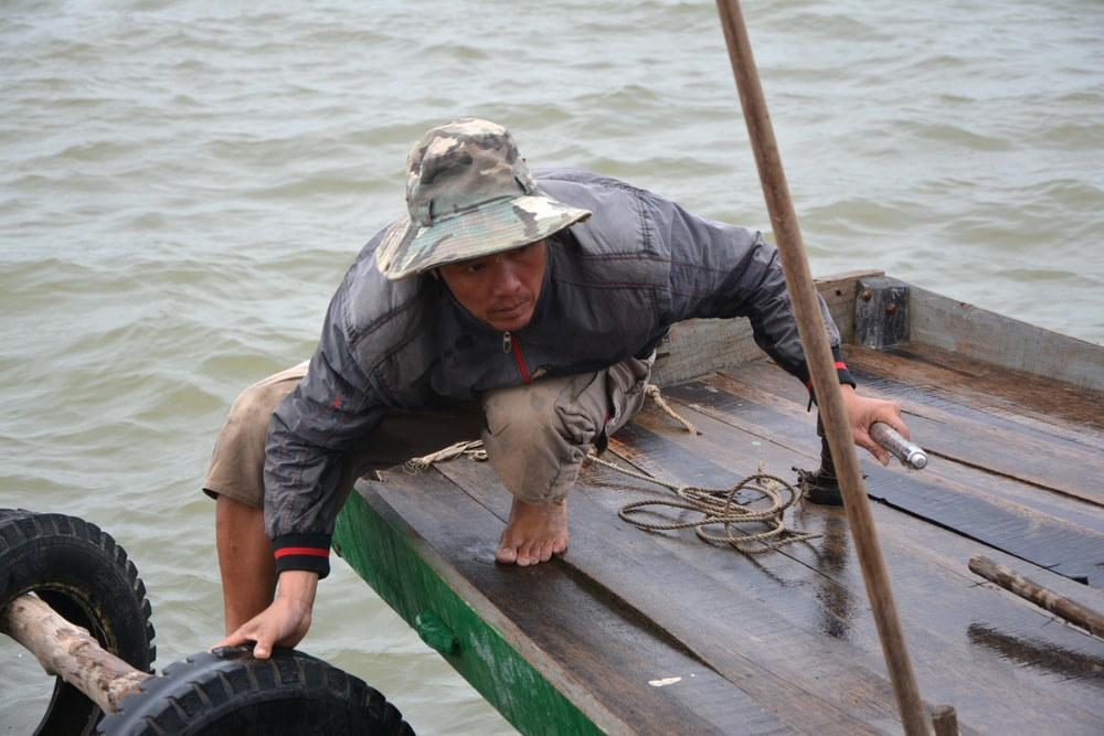 man in grey jacket and grey pants sitting on green wooden boat during daytime