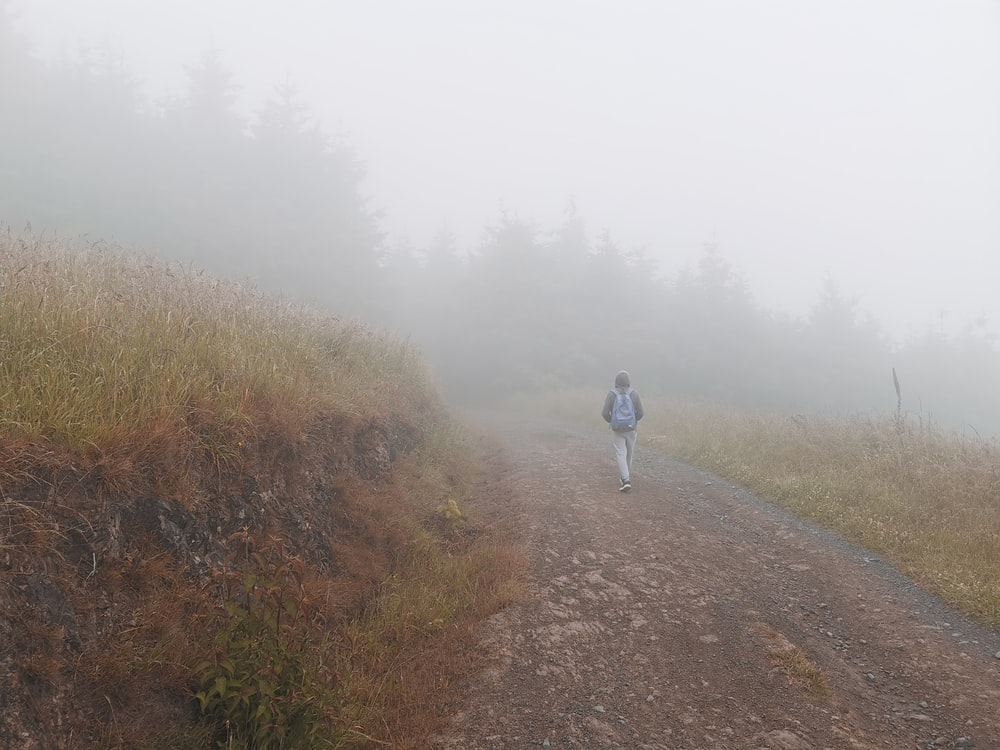 person in white jacket walking on dirt road during foggy weather