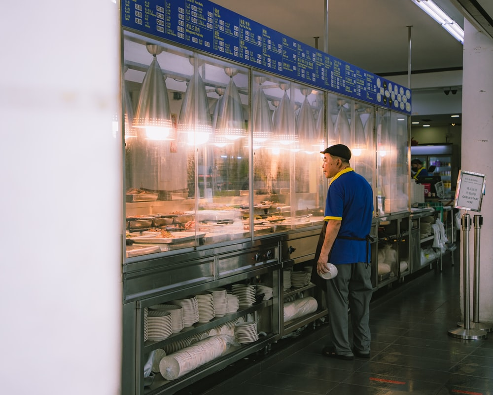 man in blue shirt standing in front of clear glass display counter
