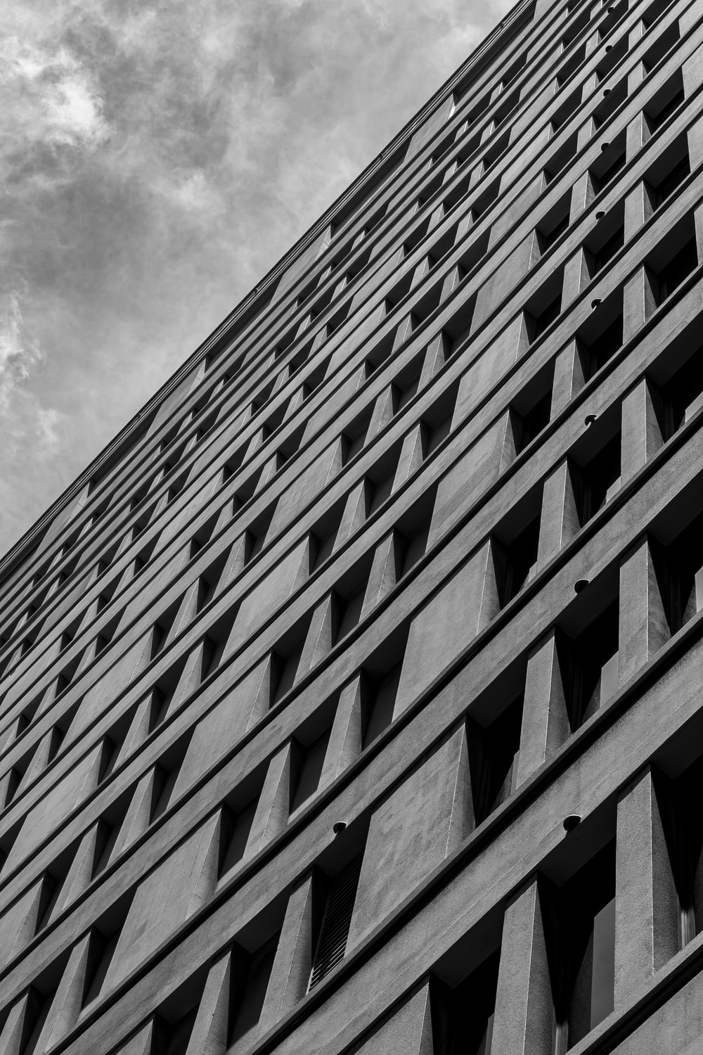 grayscale photo of concrete building under cloudy sky