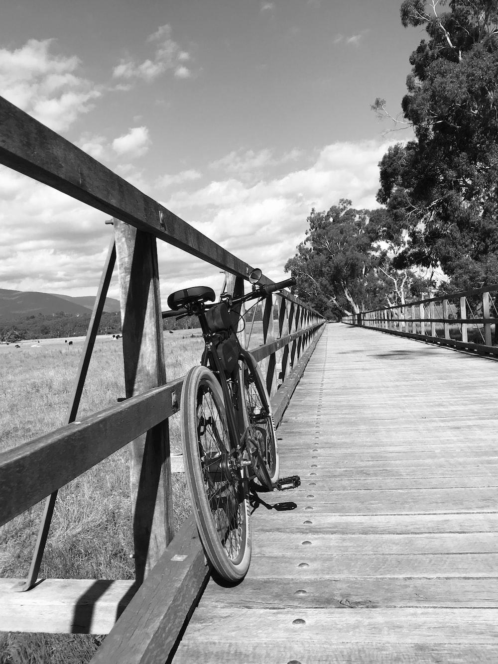 grayscale photo of bicycle on wooden bridge