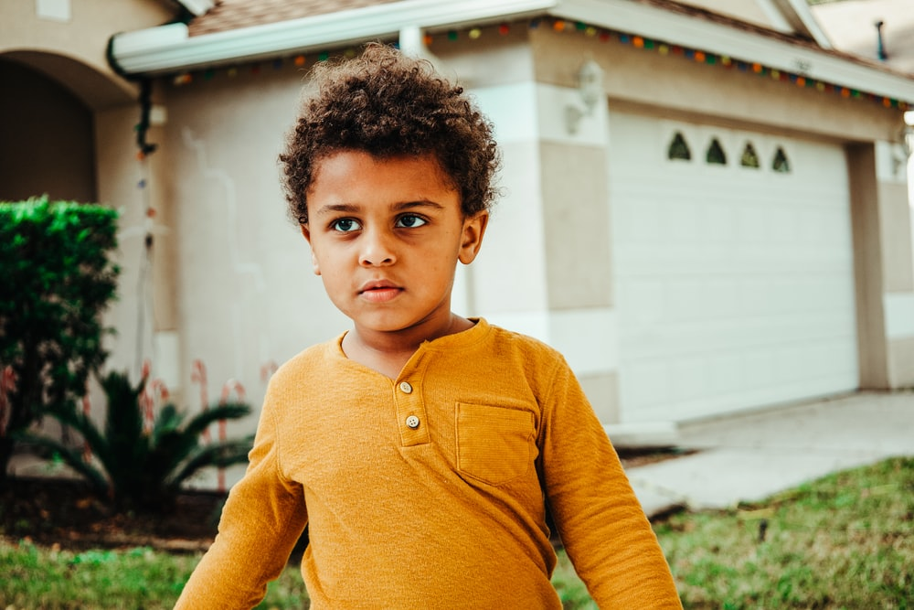 boy in yellow henley long sleeve shirt standing near white building during daytime