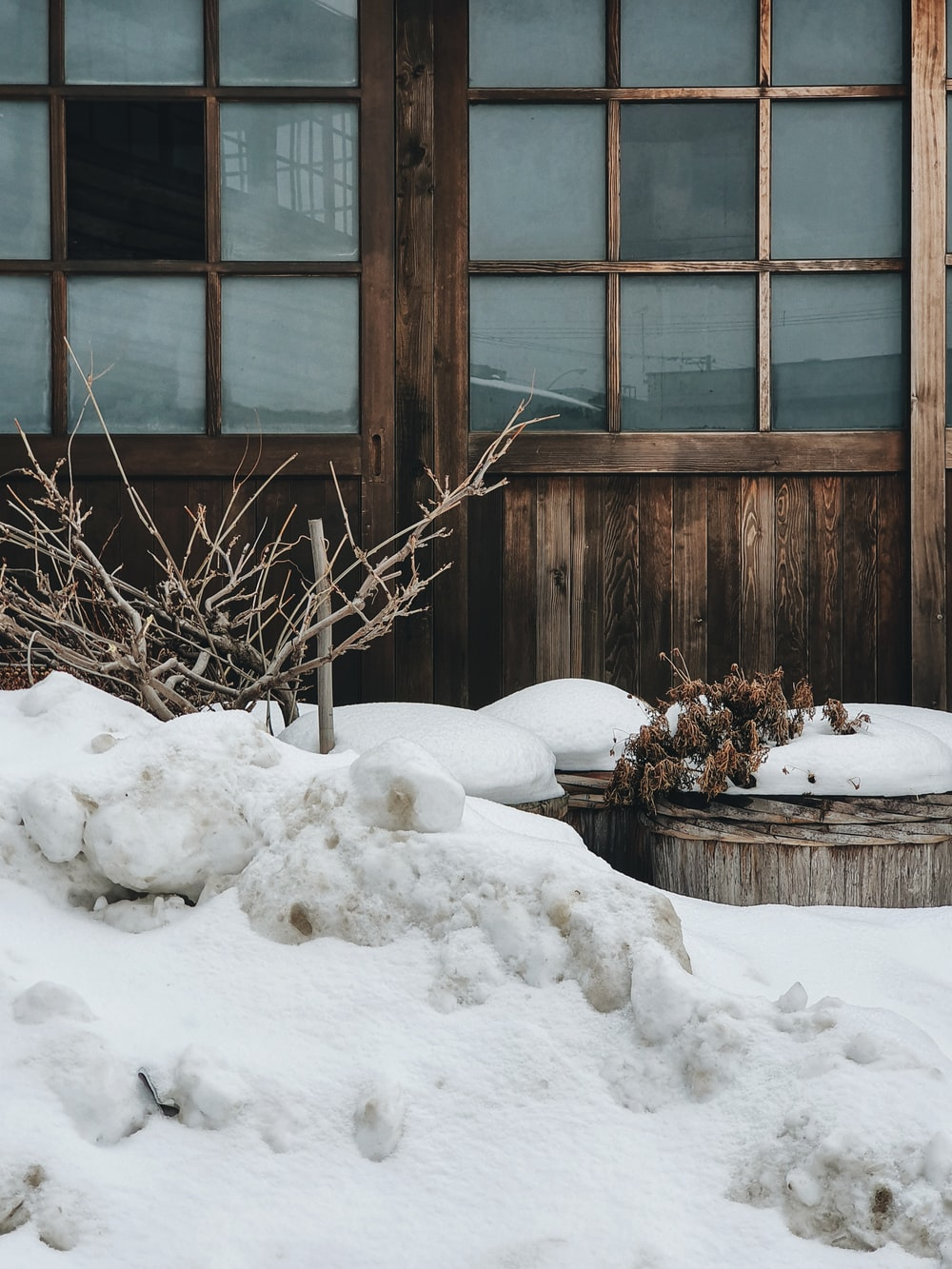 brown wooden framed glass window covered with snow
