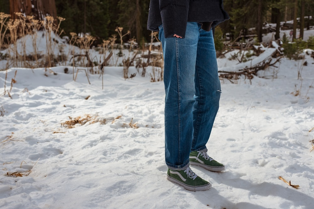 person in blue denim jeans and black jacket standing on snow covered ground during daytime