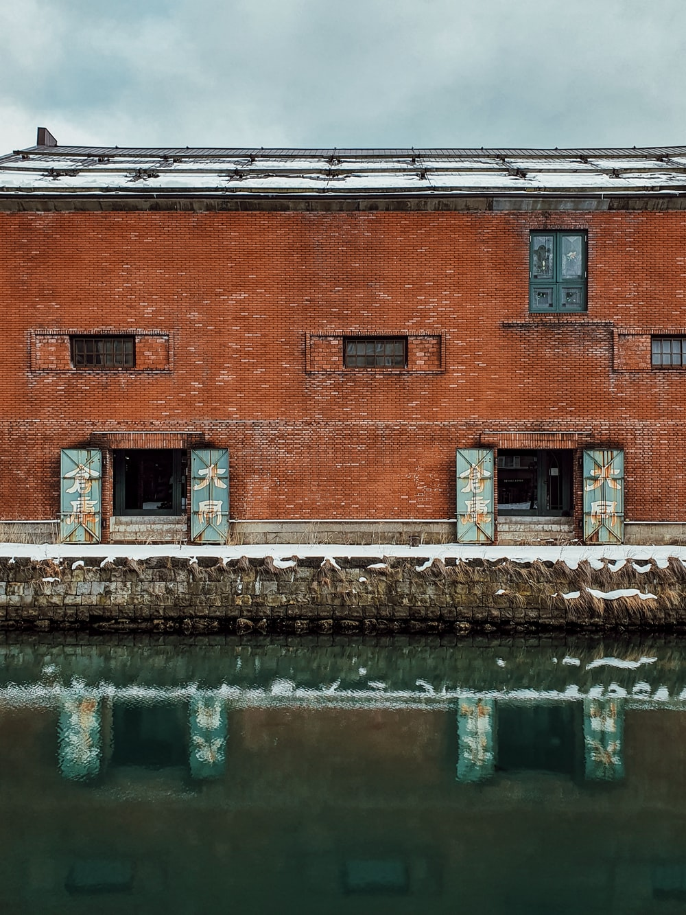 brown brick building beside body of water during daytime
