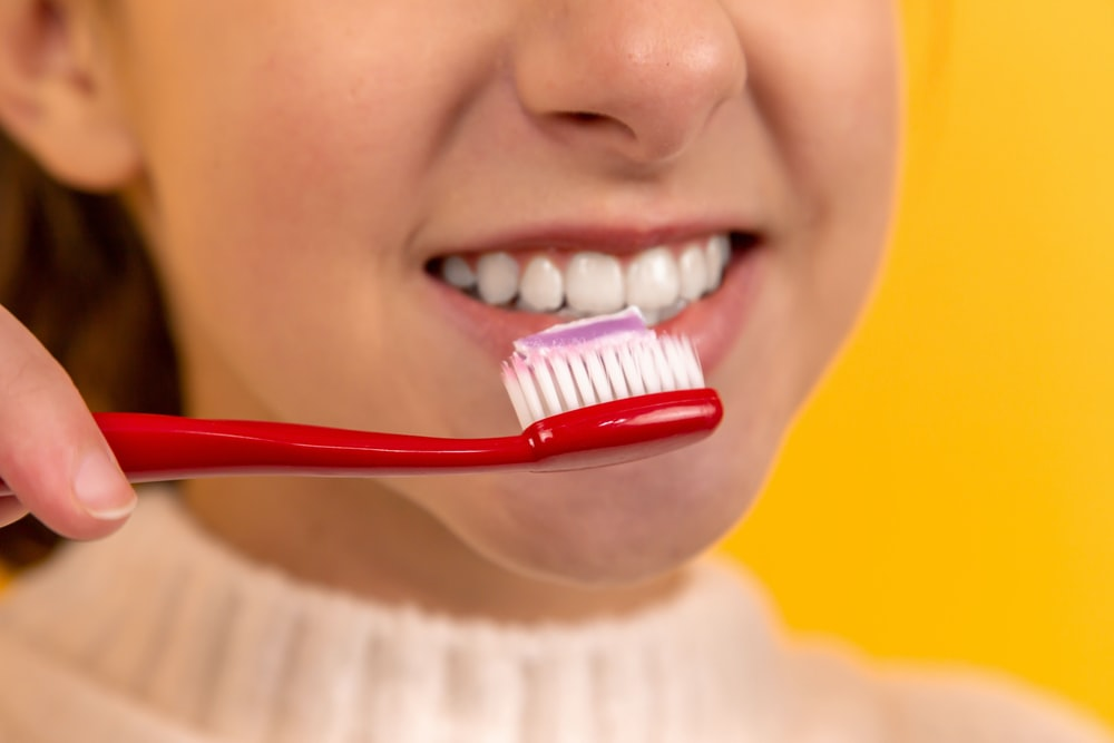 girl with red and white toothbrush in mouth