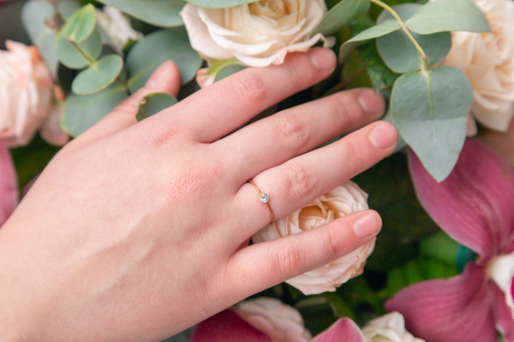 person wearing gold wedding band holding white rose