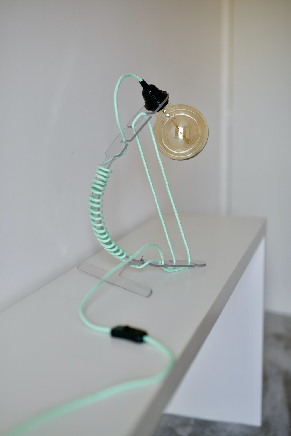 green and black earphones on white wooden table