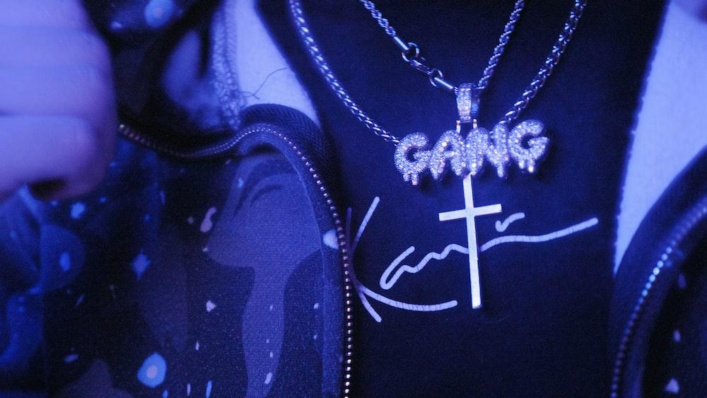 silver cross pendant necklace on black textile