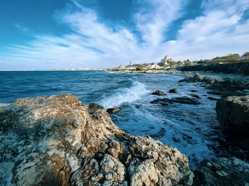 ocean waves crashing on rocky shore under blue and white cloudy sky during daytime
