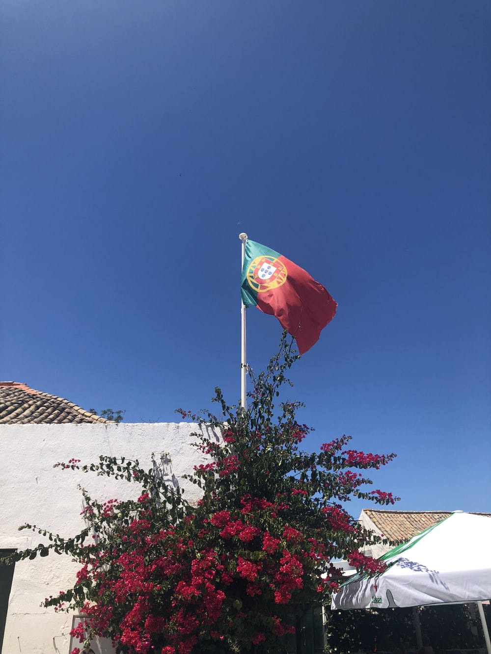 red and white flag on white concrete wall under blue sky during daytime