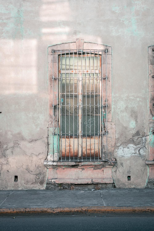 blue metal window grill on gray concrete wall