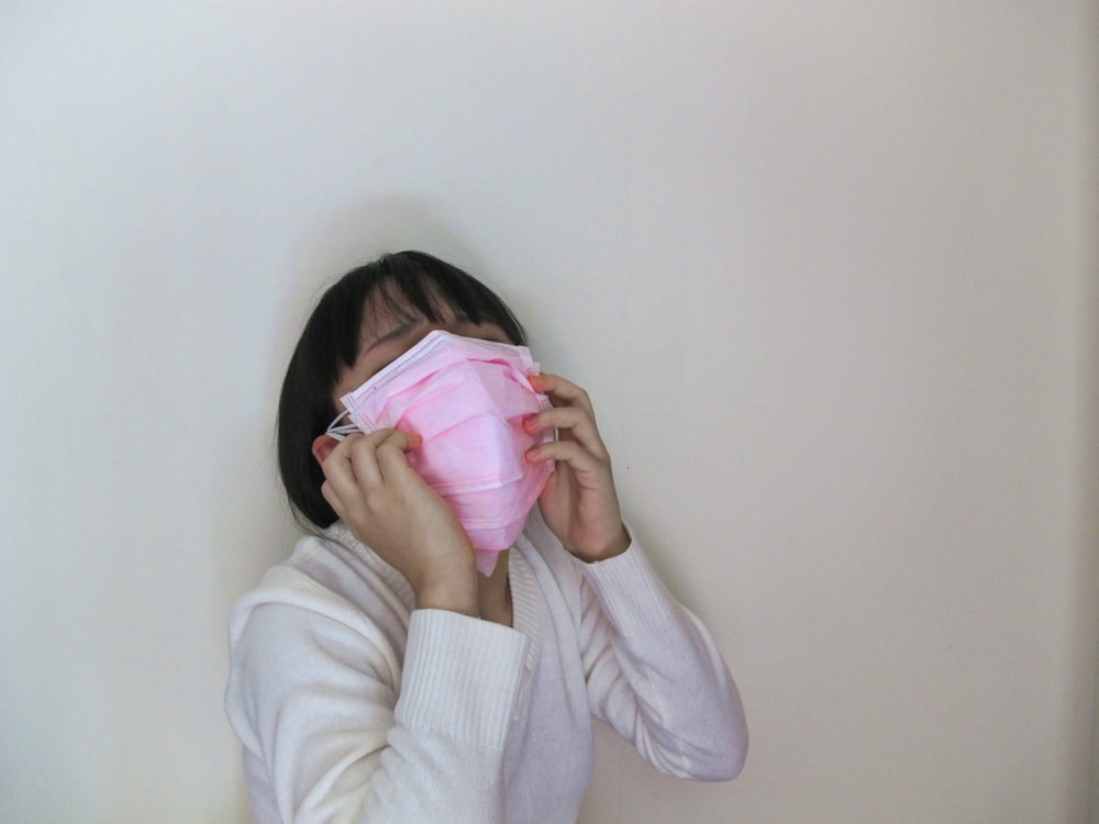 woman in white long sleeve shirt covering her face with pink textile