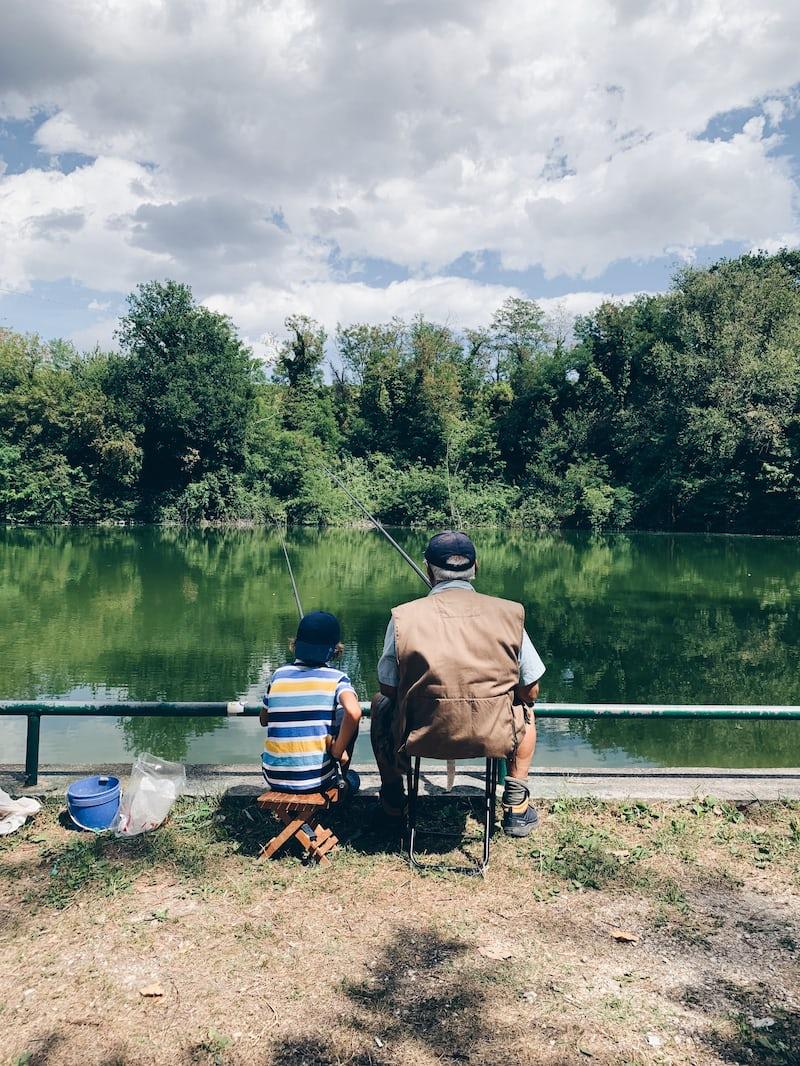湖畔で魚釣りをするおじいさんと孫