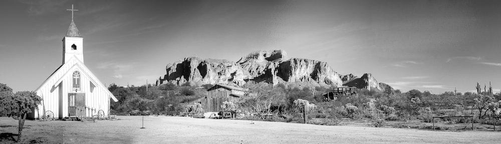 grayscale photo of house near mountain