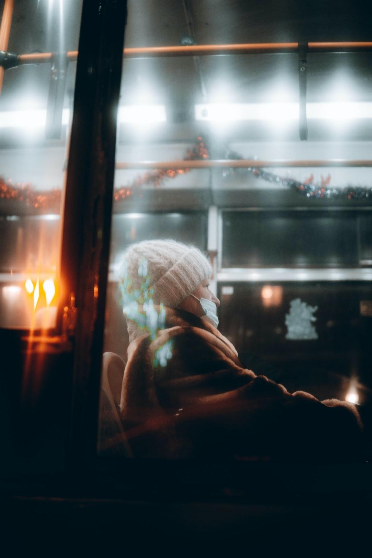 woman in white knit cap standing near window