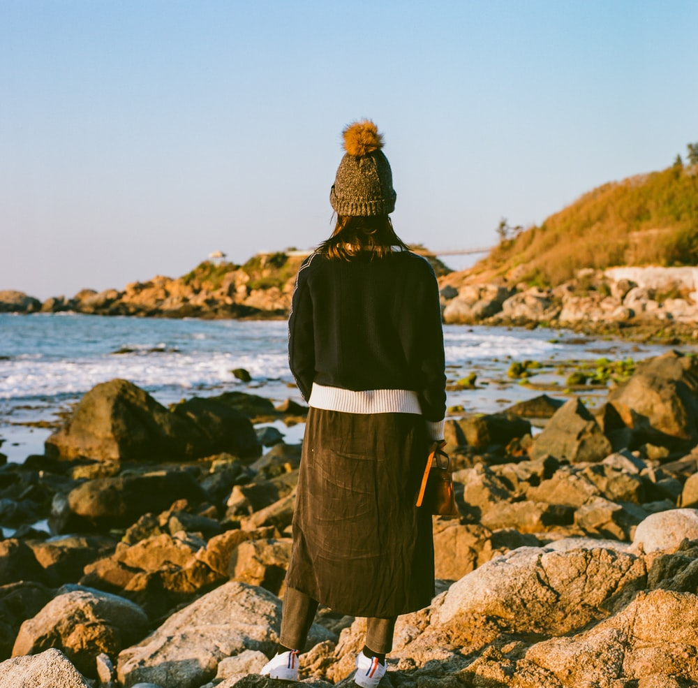 woman in black jacket standing on rocky shore during daytime