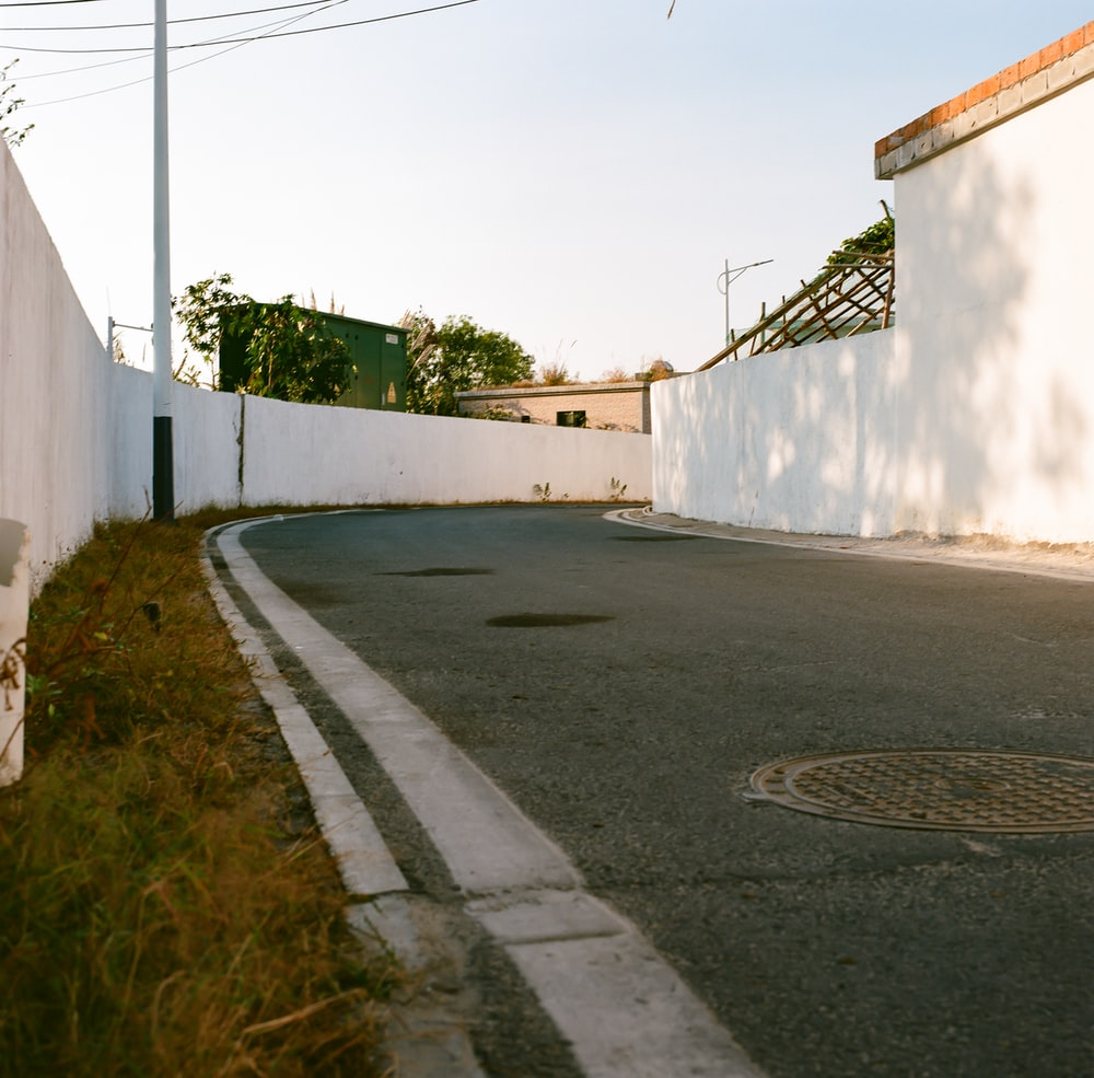 white concrete wall beside green grass during daytime