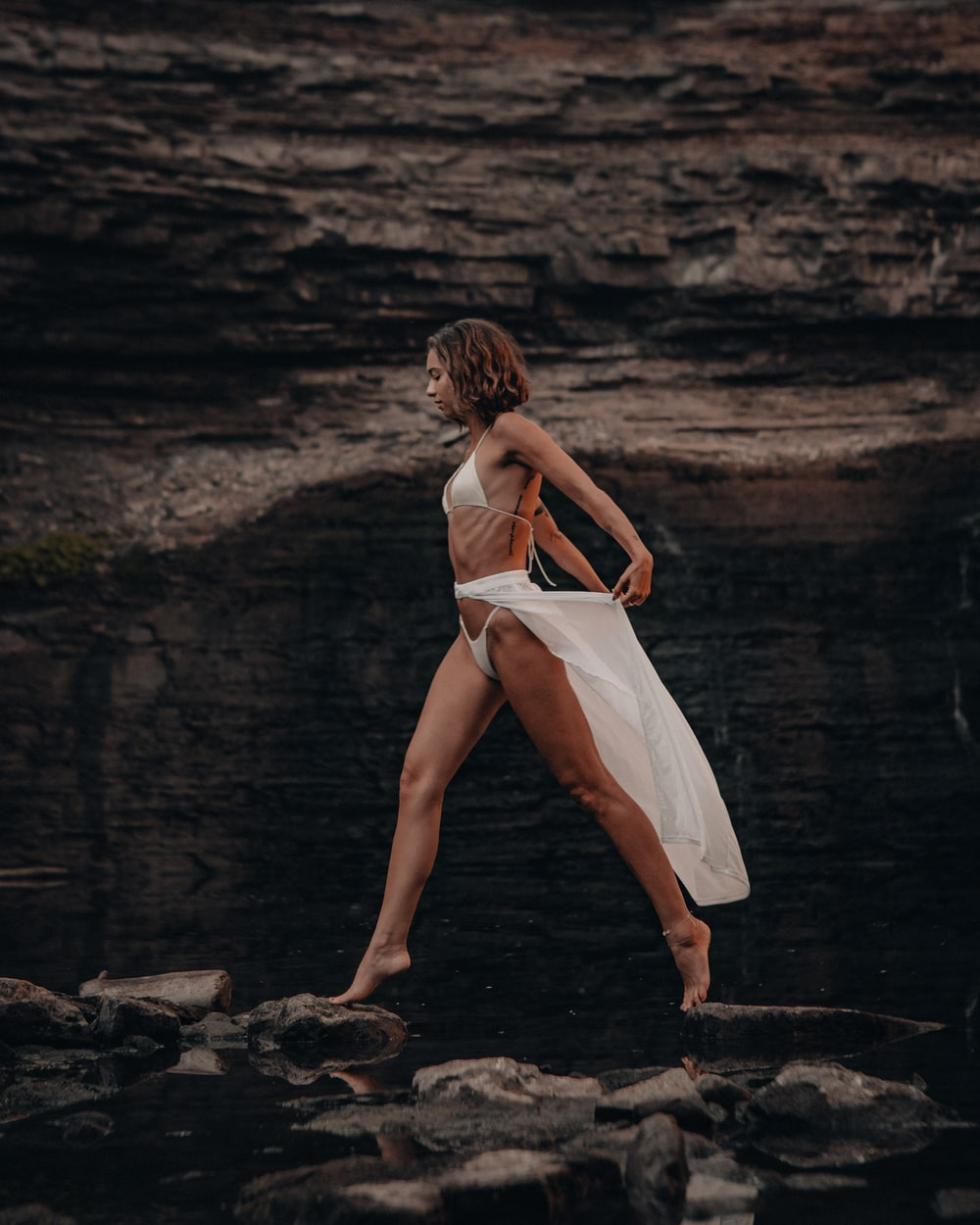 woman in white dress walking on rocky shore during daytime