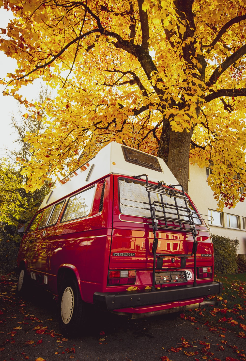 red van parked beside yellow leaf tree