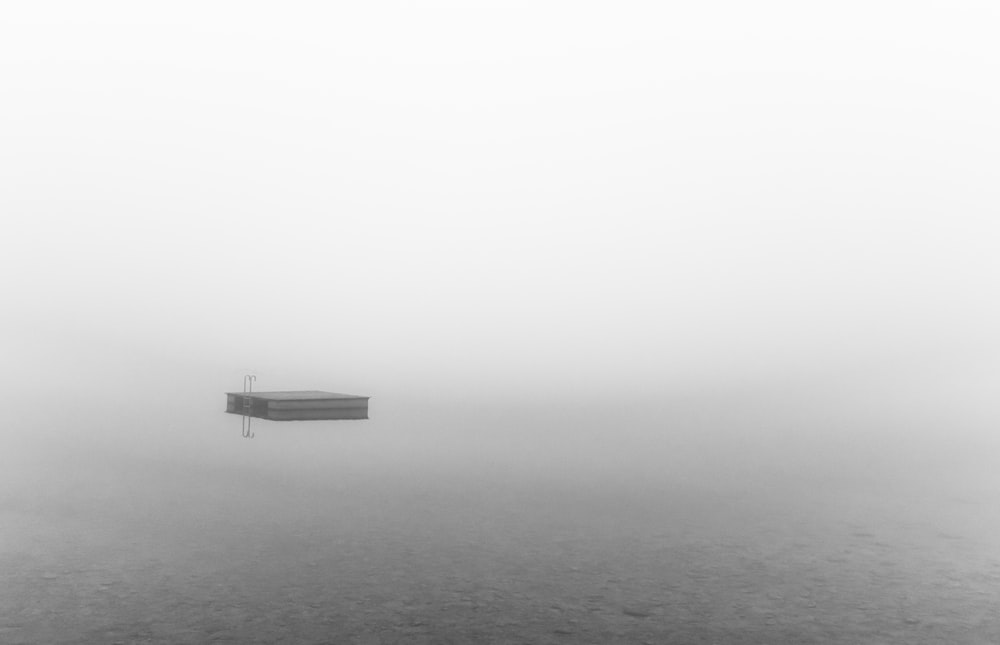 boat on body of water during foggy weather