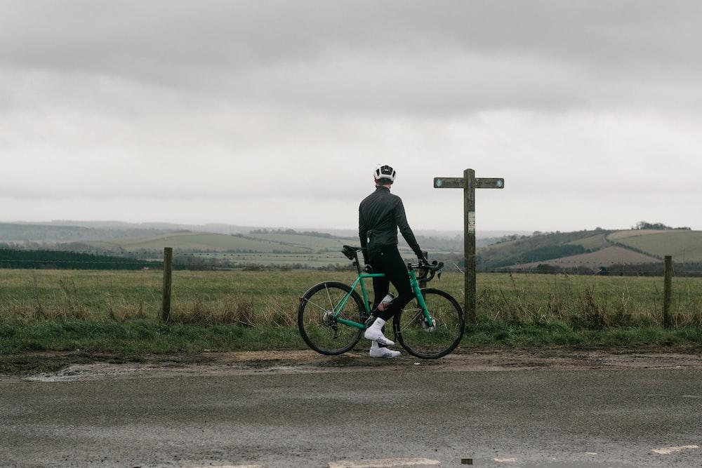 man in black jacket riding on green mountain bike on road during daytime