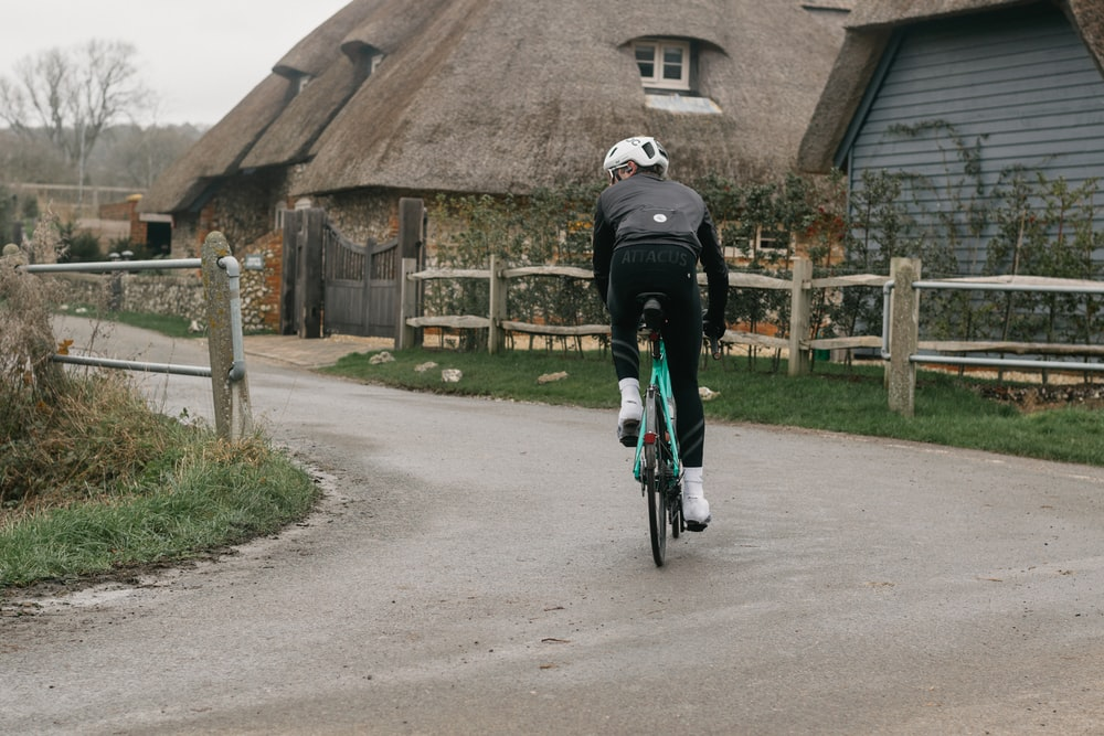 man in black jacket riding bicycle on gray concrete road during daytime