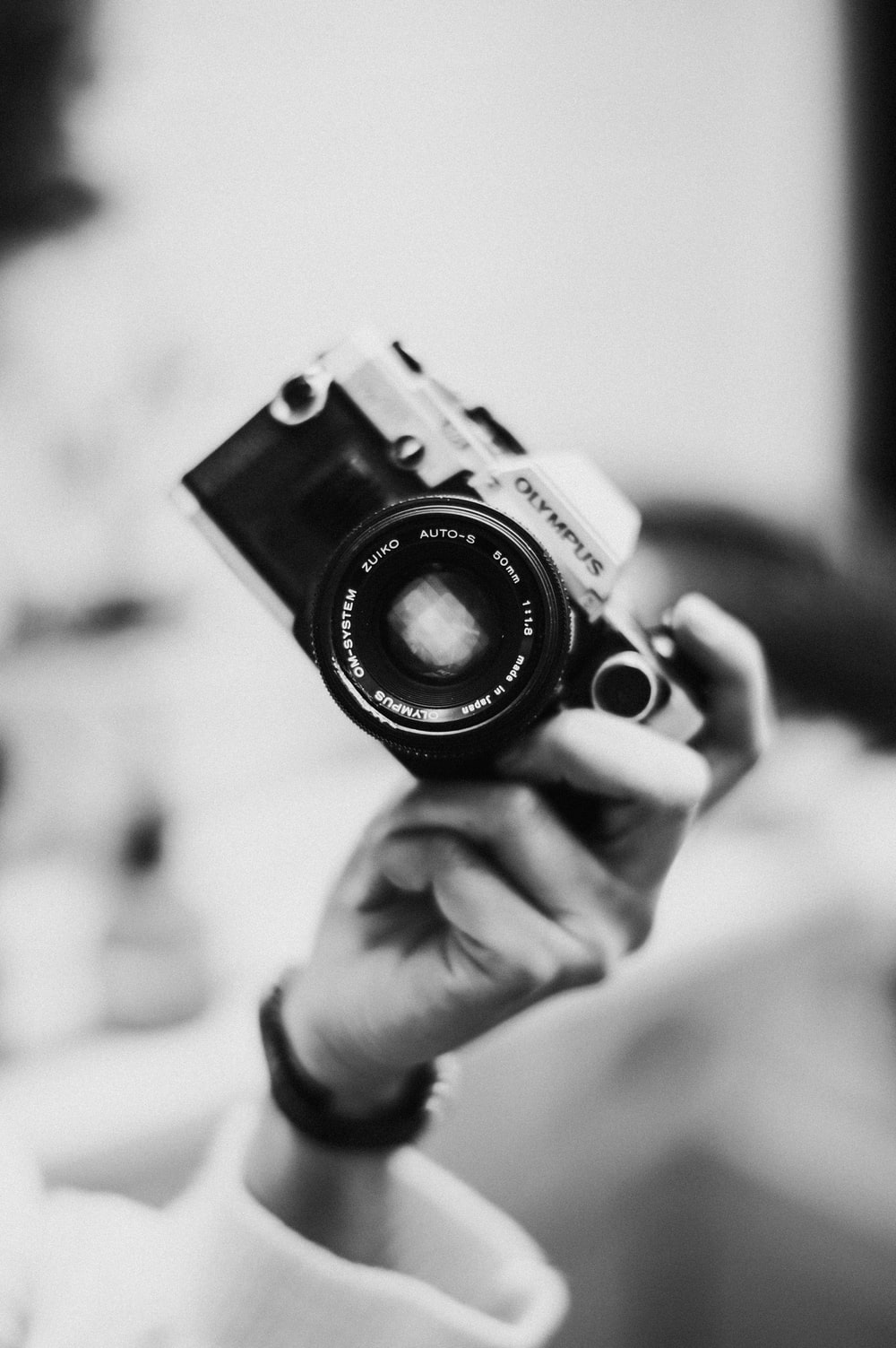 grayscale photo of person holding camera