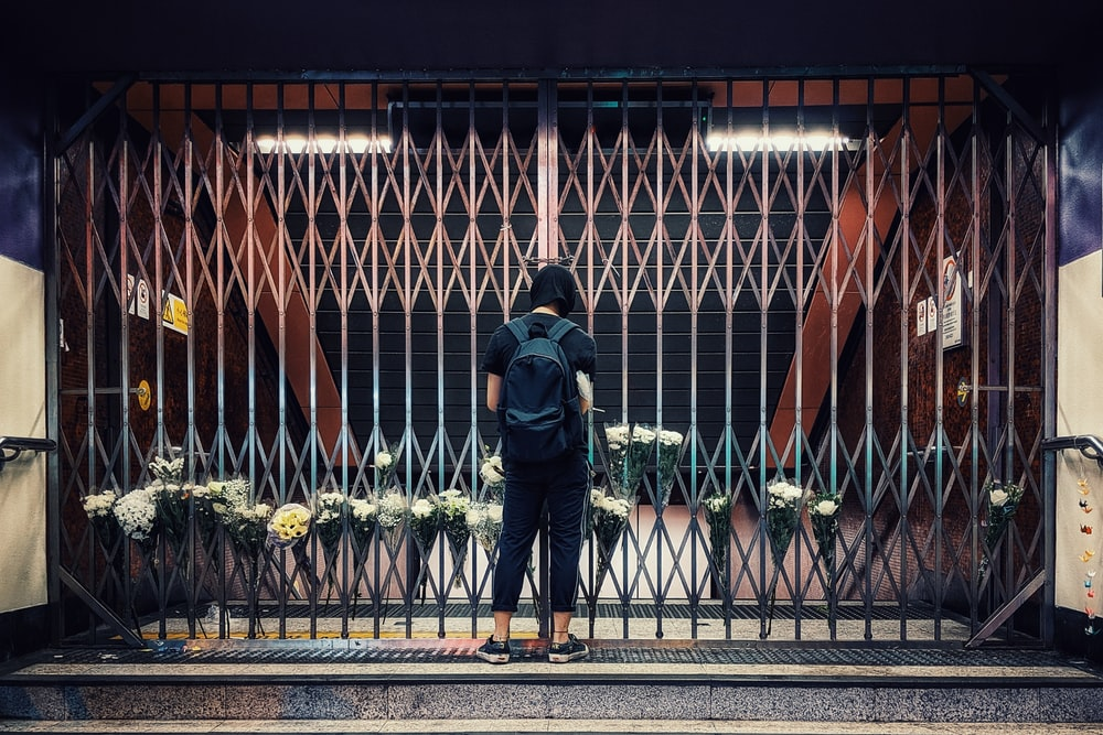 man in black jacket and blue denim jeans standing in front of black metal fence