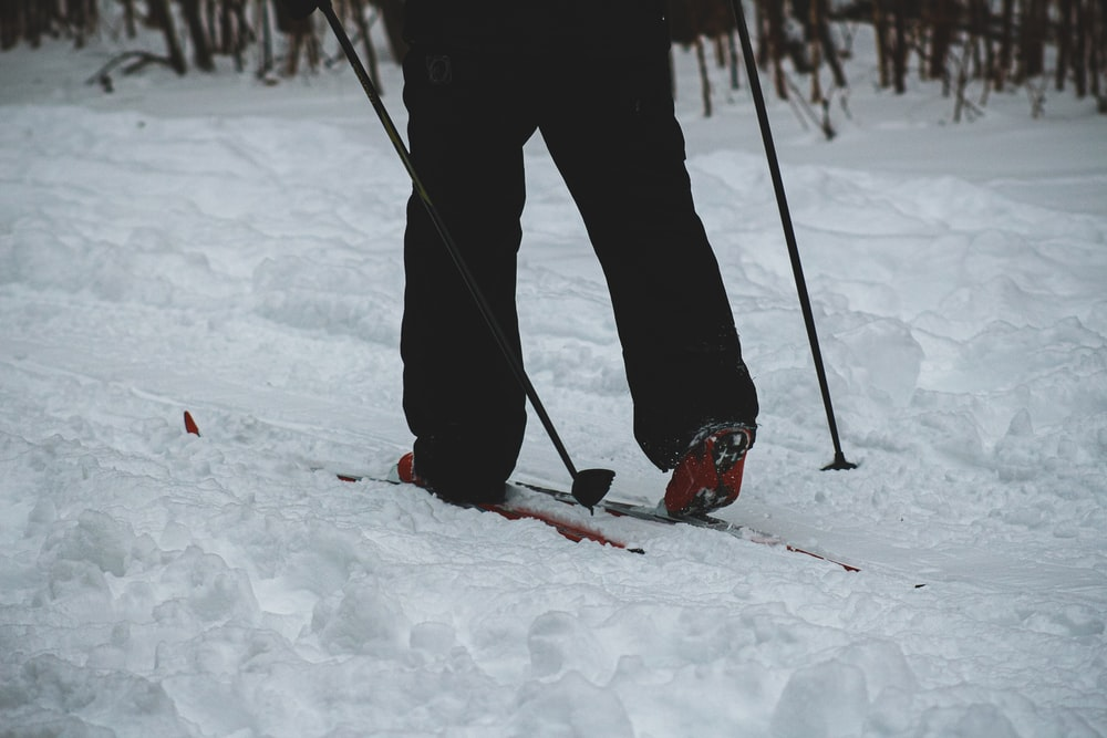 person in black pants and red snow ski